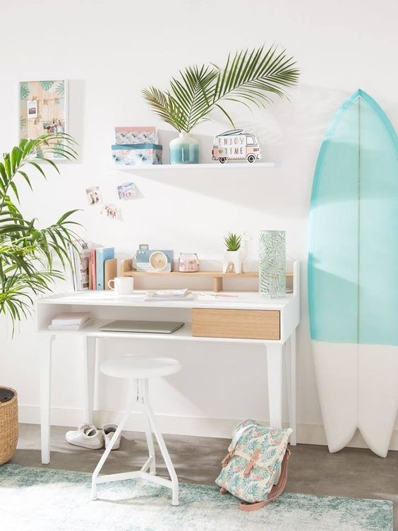 Surf board next to a desk creating a modern wall decor